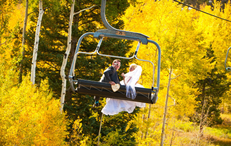 Bride and groom on the ski lift in the mountains