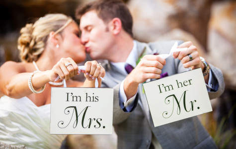 Bride and groom kissing and holding signs
